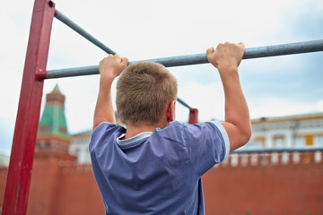 Boy does chin-ups against kremlin wall, back view