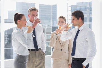 Smiling team of business people drinking champagne