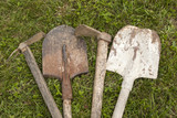 Used farm hand implements on green grass background poster