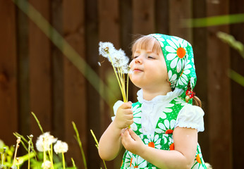 portrait of a girl who is holding a dandelion