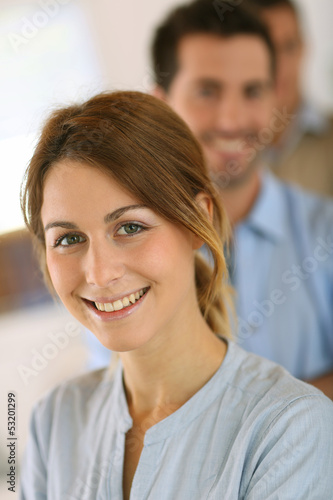 Cheerful young girl standing in front of business team