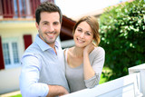 Cheerful couple standing in front of new house