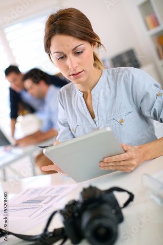Girl in office working on digital tablet