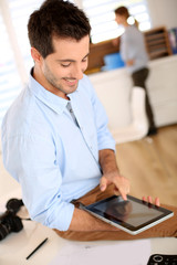 Trendy guy working in office with tablet