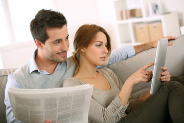 Couple reading news on both press and internet