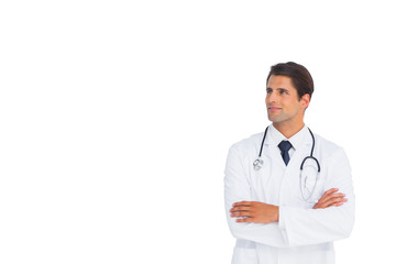 Happy doctor with arms crossed looking up