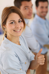 Cheerful girl in office showing thumbs up