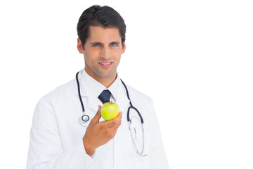 Doctor holding an apple and smiling at camera
