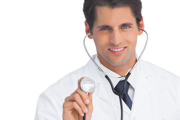 Doctor smiling and holding up stethoscope