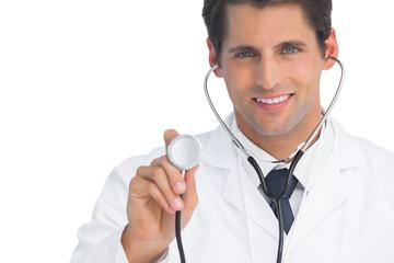 Smiling doctor holding up stethoscope
