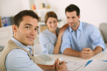 Smiling financial adviser with young couple