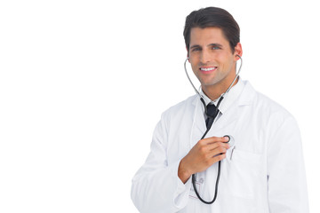 Happy doctor holding up stethoscope to his chest