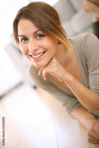 Smiling girl relaxing on the floor at home