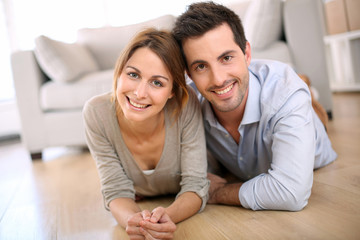 Cheerful couple laying on the floor at home