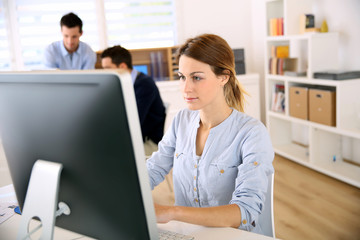 Young woman in office working on desktop