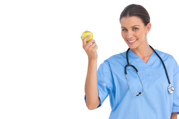Happy surgeon holding an apple and smiling at camera