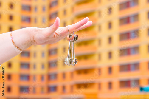 Hand holding keys house