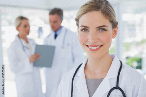 Smiling blonde haired doctor standing in her office