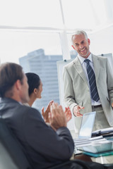 Colleagues applauding the manager during a meeting