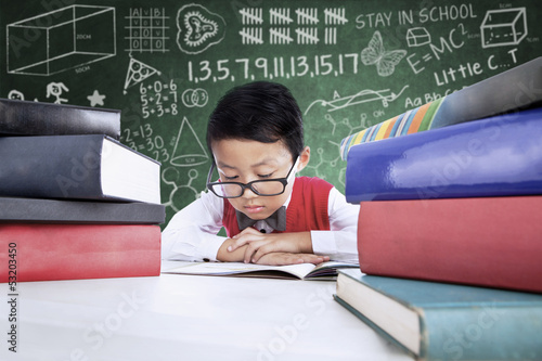 Close-up boy student reading books in class