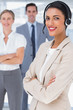 Smiling businesswoman with headset crossing her arms