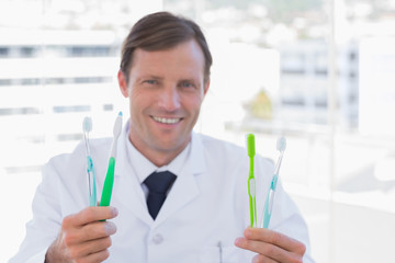 Smiling doctor holding two toothbrushes