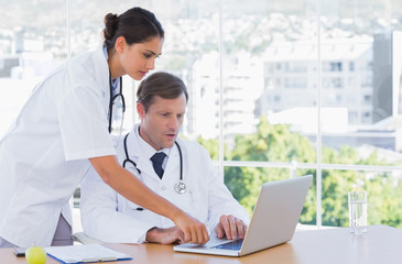Group of doctors working together on a laptop