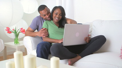 Cute black couple using a laptop in living room