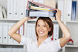 Smiling businesswoman with folders over head
