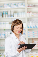 Smiling pharmacist using a tablet-pc