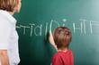 Young boy writing on the blackboard