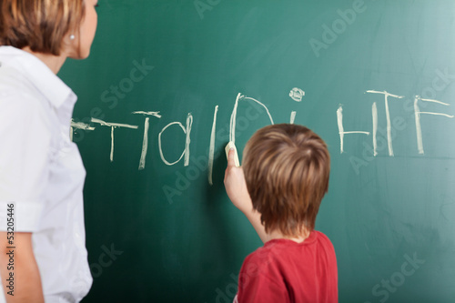 Young boy writing on the blackboard