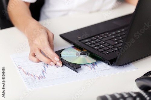 Woman inserting a cd in her laptop
