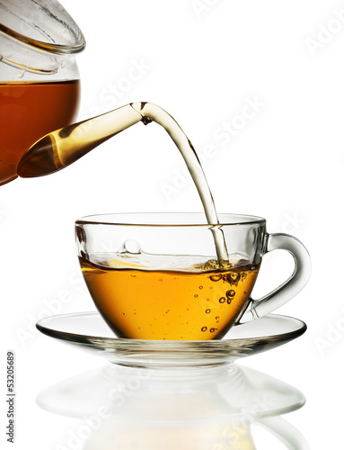 Tuinposter Thee Tea pouring into glass cup isolated in white