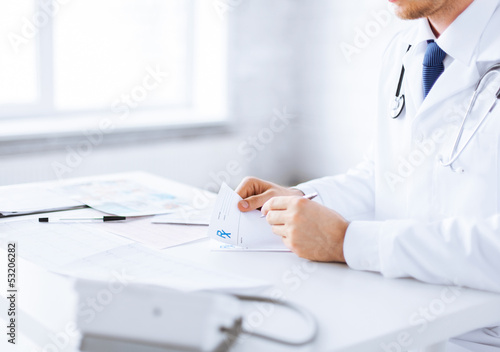 male doctor writing prescription paper