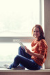 Girl sits on window sill and works with tablet