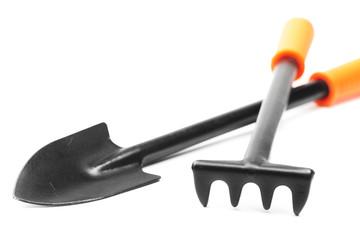 small garden tools: spade and rake on white
