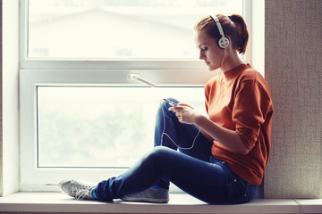 Girl sits on window sill and listens to music