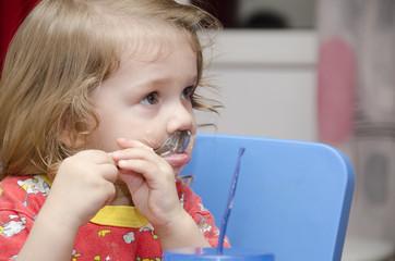 Девочка облизывает ложку, кушает торт, и смотрит вправо