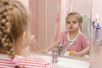 Четырехлетняя девочка полоскает зубы после чистки в ванной