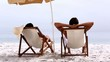 Couple relaxing under parasol