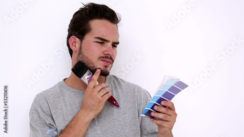 Thoughtful man looking at colour chart