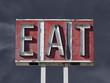 Vintage Eat Sign with Dark Thunderstorm Sky
