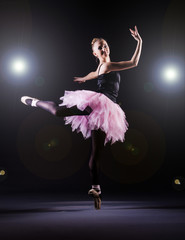 Ballerina dancing in the dark studio