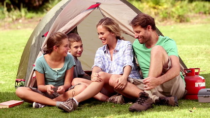 Family sitting in front of their tent spending time together