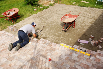 Man laying down paver