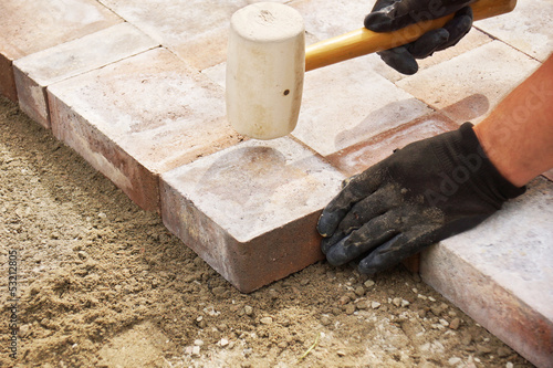 Using a mallet to set paver