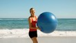 Woman playing  with her fitness ball on the beach