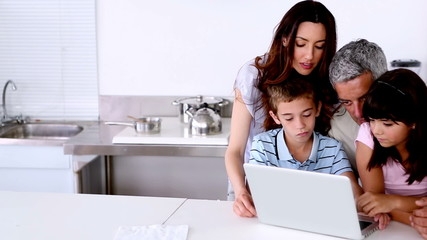 Family looking at laptop on the kitchen