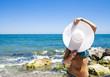 Ragazza carina con cappello bianco con sfondo di mare